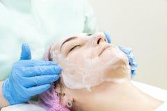 Masque cosmétique de processus de massage et de massages faciaux photographie stock