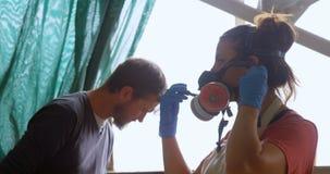 Masque de gaz de port de femme dans l'atelier 4k banque de vidéos
