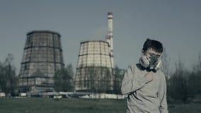 Masque de gaz de port de jeune garçon contre des cheminées d'usine Le garçon suffoque en raison de la pollution Toux de type banque de vidéos