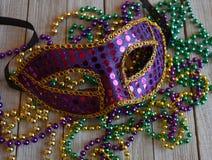 Masque de Mardi Gras avec des perles sur un fond en bois Photos stock