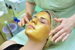Masque de massage facial d'or Images stock