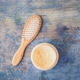 Masque de peigne cuir chevelu et de brosse et de cheveux en bois de massage et de cheveux sur le fond rustique Images stock