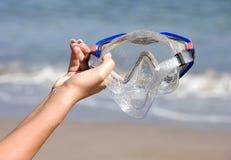 Masque de scaphandre de fixation de main de Womans sur la plage tropicale Photo stock