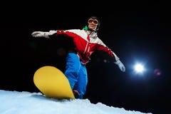 Masque de ski de port de jeune homme équilibrant sur le surf des neiges Photos stock