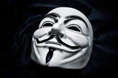 Masque de vendetta sur le fond noir Ce masque est un symbole bien connu pour le hacktivist en ligne Images stock