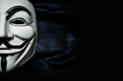 Masque de vendetta sur le fond noir Ce masque est un symbole bien connu pour le hacktivist en ligne Photographie stock libre de droits