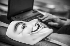 Masque de vendetta sur le vieux fauteuil dans l'usine abandonnée avec la femme sur le fond avec l'ordinateur photographie stock libre de droits