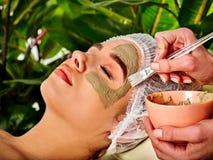 Masque facial de boue de femme dans le salon de station thermale Massage de visage photo stock