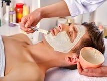Masque facial de boue de femme dans le salon de station thermale Massage de visage photographie stock libre de droits