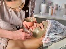 Masque facial de boue de femme dans le salon de station thermale Massage de visage image libre de droits