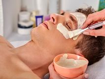 Masque facial de boue de femme dans le salon de station thermale Massage de visage image stock
