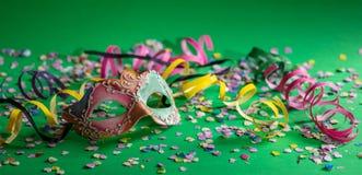 Masque, flammes et confettis de carnaval sur le fond vert clair image libre de droits