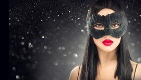 Masque foncé de port de carnaval de femme de brune de charme de beauté, partie au-dessus de fond de noir de vacances photos stock