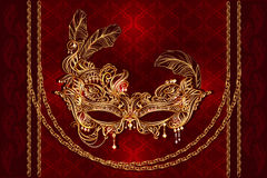 Masque mardi gras. Luxury gold Venetian carnival mask with golden chains, feathers and pearls on a red velvet satiny