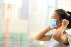 Masque protecteur asiatique d'usage de femme dans la ville Photographie stock libre de droits