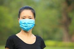 Masque protecteur asiatique d'usage de femme dans la ville Image stock