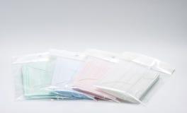 Masque protecteur jetable de boucle verte, rose, bleu-clair et blanche d'oreille dans le recouvrement de sachet en plastique, uti Image libre de droits