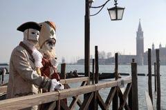 Masque vénitien de port de personne et pose le long du waterfr de St Mark Images libres de droits