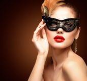 Masque vénitien de port de carnaval de mascarade de femme modèle de beauté à la partie d'isolement sur le fond noir Noël et nouve Images libres de droits