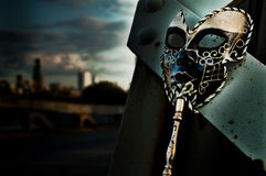 Masquerade. Venetian Mask on Vintage Bridge with City Skyline royalty free stock photos