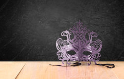 Филигранная загадочная венецианская маска masquerade на деревянном столе и предпосылке текстуры черной Стоковое Изображение RF