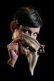 Masquerade. A young women is peeking from behind an original venice-stlye mask Royalty Free Stock Image