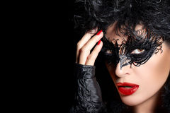 Masquerade. High Fashion Portrait of Mysterious Woman with Black. Masquerade. Pretty short hair mysterious woman wearing trendy black mask and mittens. lips and royalty free stock photography