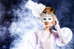 Masquerade mask. Portrait of a beautiful fashion model in the refined white dress and elegant hat. Carnival, masquerade Royalty Free Stock Images
