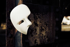 Masquerade - Phantom of the Opera Mask. On Rusty Bridge Column Stock Photo