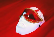 Masquerade And Theater Masks On the Red Background. Masquerade mask lies on a white plastic mask closeup on a red silk background. Selective focus, space for royalty free stock images