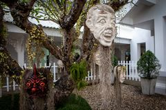 Masques effrayants accrochant sur des arbres chez Wat Rong Khun - le temple blanc - un jour nuageux Chiang Rai images stock