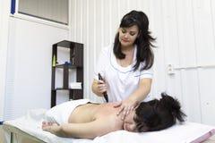 Massör som använder pinnar för att massera kvinnlign arkivbilder