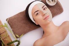 Massör som gör massage huvudet av en asiatisk kvinna i brunnsortsalongen Fotografering för Bildbyråer
