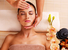 Massör som gör massage huvudet av en kvinna i brunnsortsalong Fotografering för Bildbyråer
