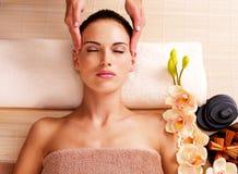 Massör som gör massage huvudet av en kvinna i brunnsortsalong Royaltyfri Fotografi