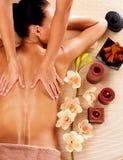 Massör som gör massage på kvinnabaksida i brunnsortsalong Arkivbild
