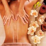 Massör som gör massage på kvinnabaksida i brunnsortsalong royaltyfria bilder
