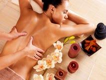 Massör som gör massage på kvinnabaksida i brunnsortsalong arkivfoto