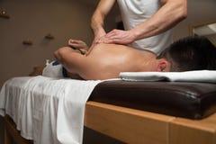 Massör som tillbaka ger massage till en man royaltyfri fotografi