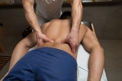 Massör som tillbaka ger massage till en man arkivfoto