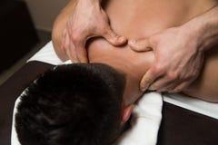 Massör som tillbaka ger massage till en man arkivbild