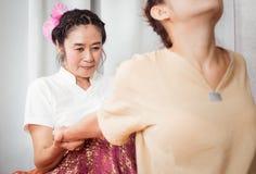 Massören drar kvinnaarmen för massagen som sträcker i thailändska Spa fotografering för bildbyråer