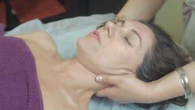 Massösen gör att läka massage av halsen till den unga kvinnan i yrkesmässig salong arkivfilmer