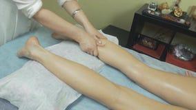 Massösen gör avslappnande massage av det vänstra benet till den unga kvinnan i salong slå stock video