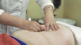 Massösen gör massage av den köttlika magen till den vuxna kvinnan i yrkesmässig salong lager videofilmer
