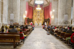 Mass blurred. Blurred picture of a mass in a catholic cathedral. Christian ceremony of the sacred mass royalty free stock photos