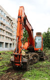 Mass cutting of adult poplars in the city. The excavator with bucket moves the wooden pieces Royalty Free Stock Photo