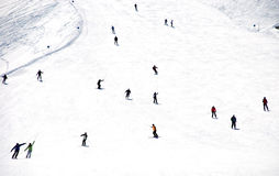 Mass descent of mountain skiers  from hillside Stock Photo