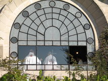 Mass in Dominus Flevit Church. View through window - priests celebrating holy mass in dominus Flevit church. Located on the Mount of Olives immediately facing stock images