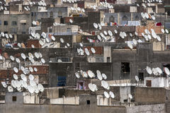 A mass of satellite discs sit atop apartment buildings in Fez in Morocco. Royalty Free Stock Image